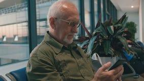 Homem superior com embarque de espera do cabelo cinzento e da barba cinzenta no aeroporto, passando o tempo usando o smartphone video estoque
