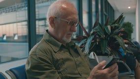 Homem superior com embarque de espera do cabelo cinzento e da barba cinzenta no aeroporto, passando o tempo usando o smartphone filme