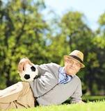 Homem superior com o chapéu que encontra-se em uma grama e que guardara uma bola de futebol mim fotos de stock