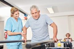 Homem superior com o fisioterapeuta na escada rolante fotografia de stock