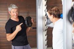 Homem superior com o instrutor da aptidão no gym Fotos de Stock Royalty Free