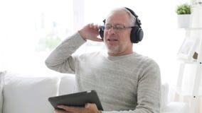 Homem superior com PC da tabuleta e fones de ouvido em casa 14 filme