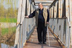 Homem superior com posição da vara de passeio em uma ponte do metal imagem de stock