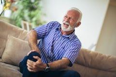 Homem superior com problemas e dor crônicos do joelho foto de stock