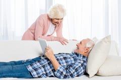 homem superior com a tabuleta que olha a esposa de sorriso próximo perto ao descansar no sofá imagem de stock royalty free