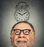 Homem superior com vidros e despertador acima de sua cabeça que olha acima Fotos de Stock Royalty Free