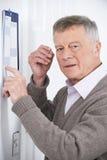 Homem superior confuso com a demência que olha o calendário de parede imagens de stock royalty free
