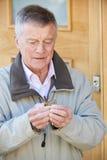 Homem superior confuso que tenta encontrar a chave da porta foto de stock royalty free