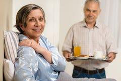 Homem superior de inquietação que traz o café da manhã à esposa Imagens de Stock