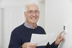 Homem superior de sorriso com Bill Adjusting Central Heating Thermosta Fotografia de Stock Royalty Free
