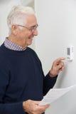 Homem superior de sorriso com Bill Adjusting Central Heating Thermosta imagens de stock royalty free
