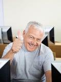 Homem superior de sorriso que gesticula os polegares acima na classe do computador fotos de stock