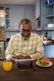 Homem superior de sorriso que usa o tablet pc na cozinha Fotografia de Stock Royalty Free