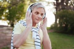Homem superior delicioso que aprecia a música nos fones de ouvido fora Fotografia de Stock