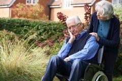 Homem superior deprimido na cadeira de rodas que está sendo empurrada por Wif imagem de stock