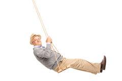 Homem superior despreocupado que balança em um balanço de madeira Foto de Stock Royalty Free