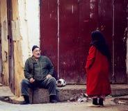 Homem superior do amigo, conversa da mulher na rua da cidade de Fes Medina com o vestido colorido tradicional de musselina e o es fotos de stock
