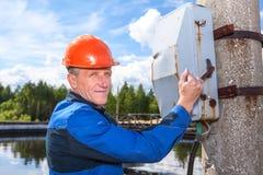 Homem superior do trabalhador que gira o interruptor de alimentação Foto de Stock