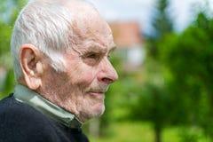 Homem superior dos anos de idade 80 positivos consideráveis que levanta para um retrato em seu jardim Imagens de Stock