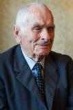 Homem superior dos anos de idade 80 positivos consideráveis que levanta para um retrato em sua casa Imagens de Stock Royalty Free