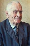 Homem superior dos anos de idade 80 positivos consideráveis que levanta para um retrato em sua sala de visitas Foto de Stock