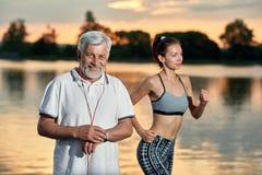 Homem superior e moça que correm perto do lago na noite fotografia de stock royalty free
