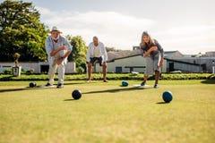 Homem superior e mulher que jogam boules em um gramado imagem de stock
