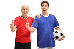 Homem superior e novo que guarda um futebol e que faz o polegar acima do sinal Fotografia de Stock