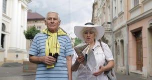Homem superior e turistas fêmeas que andam com um mapa nas mãos que procuram a rota filme