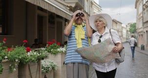 Homem superior e turistas fêmeas que andam com um mapa nas mãos que procuram a rota vídeos de arquivo