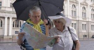 Homem superior e turistas fêmeas que andam com um mapa nas mãos que procuram a rota video estoque