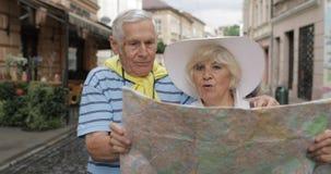 Homem superior e turistas fêmeas que estão com um mapa nas mãos que procuram a rota filme