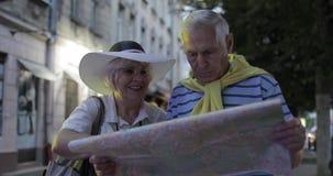 Homem superior e turistas fêmeas que estão com um mapa nas mãos que procuram a rota video estoque