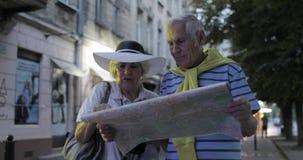 Homem superior e turistas fêmeas que estão com um mapa nas mãos que procuram a rota vídeos de arquivo