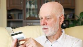 Homem superior em casa que compra em linha com o cartão de crédito no smartphone Uso da tecnologia por povos mais idosos video estoque