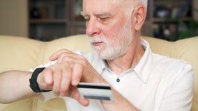 Homem superior em casa que compra em linha com o cartão de crédito no smartwatch Uso da tecnologia por povos mais idosos video estoque