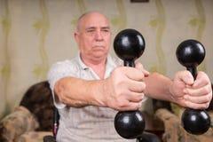 Homem superior em pesos de levantamento da cadeira de rodas em casa Imagem de Stock