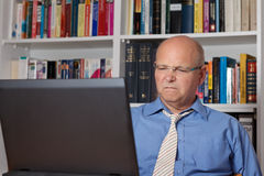 Homem superior enojado com computador Fotografia de Stock Royalty Free