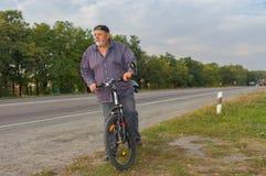 Homem superior farpado na borda da estrada que prepara-se para montar na bicicleta Imagens de Stock Royalty Free