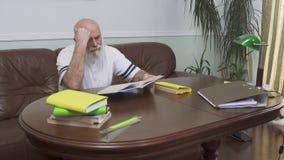 Homem superior farpado pensativo que senta-se na tabela de madeira no sofá de couro que lê o livro Ancião caucasiano que aprecia video estoque