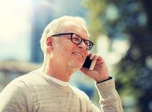 Homem superior feliz que chama o smartphone na cidade imagens de stock royalty free