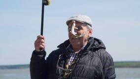Homem superior feliz que mostra um peixe recentemente travado filme