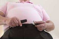 Homem superior gordo que tenta fechar sua correia Imagem de Stock