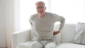 Homem superior infeliz que sofre da dor lombar em casa 133 video estoque