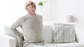 Homem superior infeliz que sofre da dor lombar em casa 134 video estoque