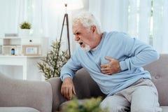 Homem superior infeliz que tem a doença cardiovascular foto de stock