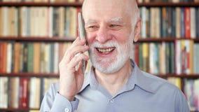 Homem superior moderno em casa que fala no telefone celular na biblioteca Estantes da biblioteca no fundo filme