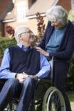 Homem superior na cadeira de rodas que está sendo empurrada pela esposa imagens de stock royalty free