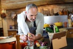 Homem superior na cozinha usando a tabuleta durante o cozimento imagens de stock royalty free