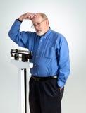 Homem superior na escala do peso Foto de Stock